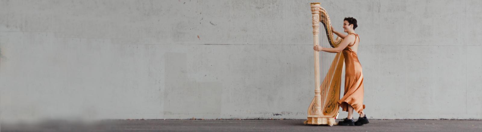 Die Harfespielerin Teresa steht mit ihrem Instrument an einer Wand