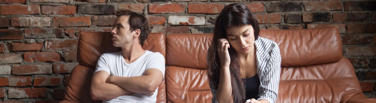 Ein Paar sitzt genervt auf einem Sofa