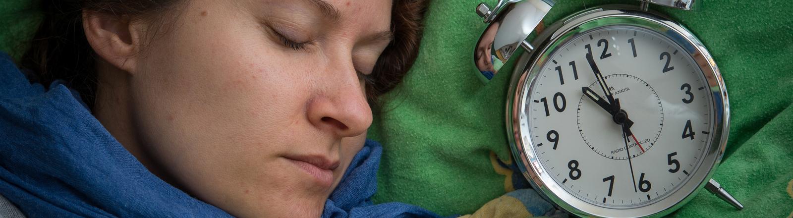 Eine Frau liegt schlafend im Bett. Neben ihr liegt ein Wecker