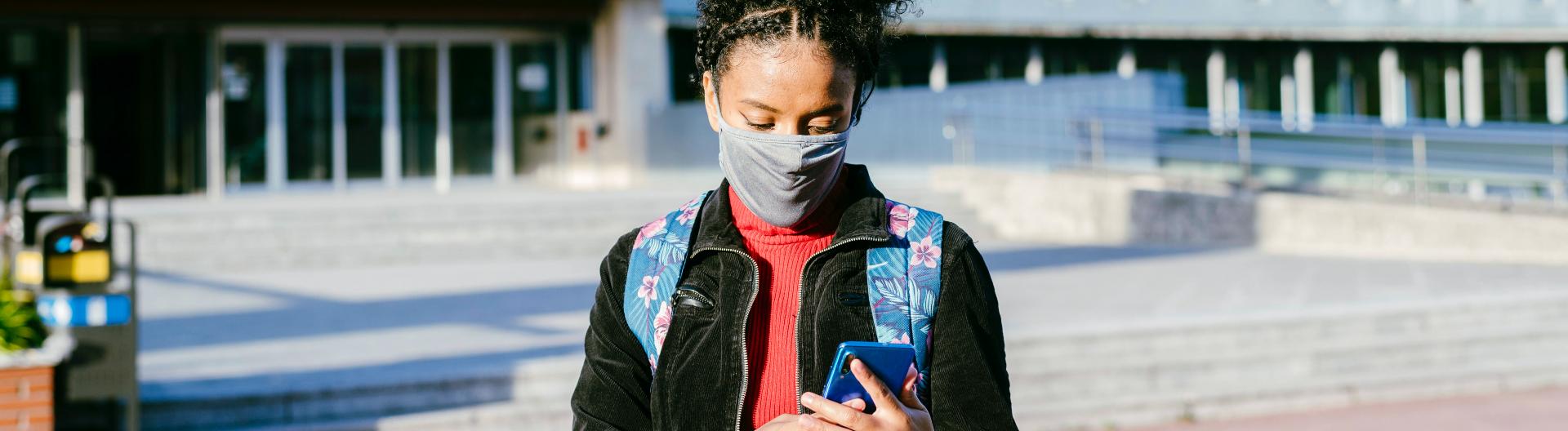 Junge Frau mit Mundschutz blickt auf ihr Smartphone
