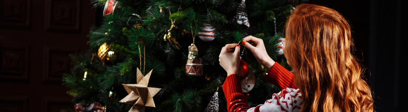 Eine Frau schmückt einen Weihnachtsbaum