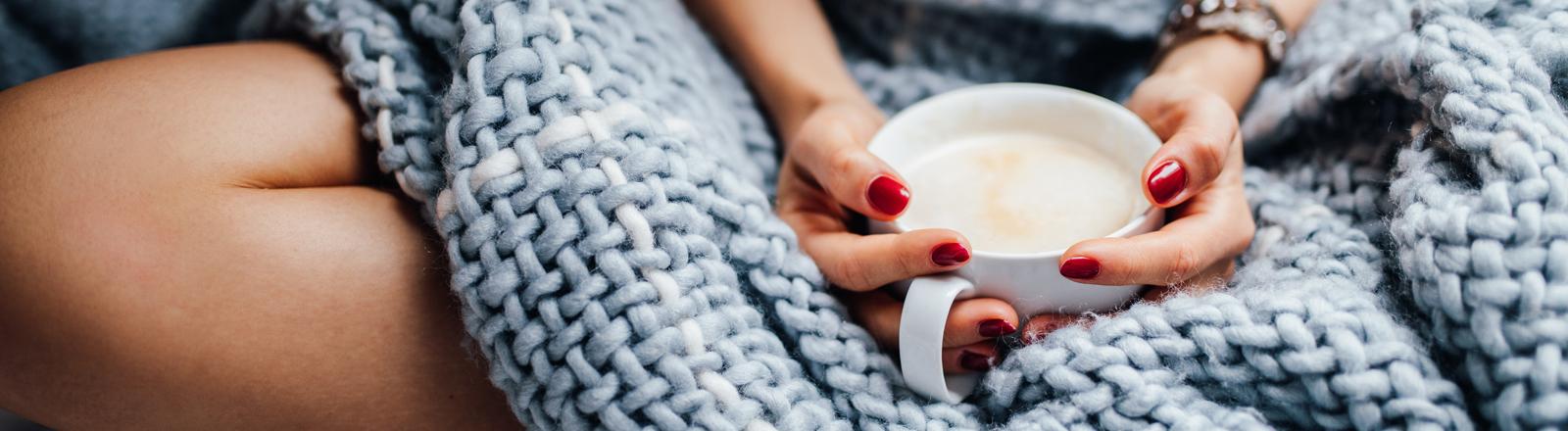 Frau in Decke gewickelt hält Tasse Kaffee in der Hand