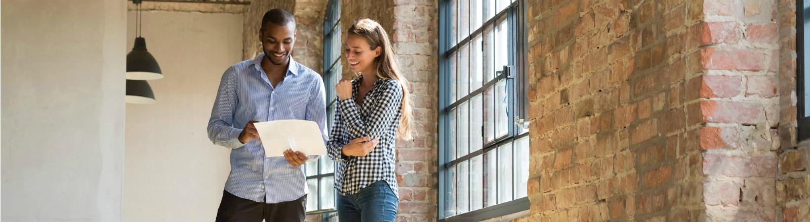 Ein Mann und eine Frau stehen in einer leeren Wohnung und schauen auf einen Zettel.