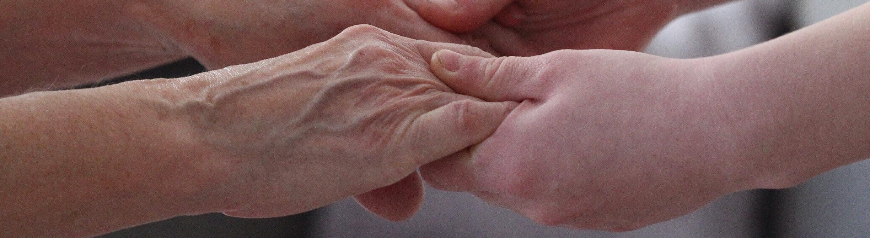 Eine alte Frau hält sich an den Händen einer jungen Frau.