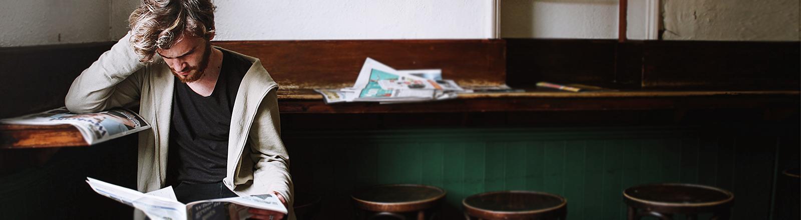 Ein junger Mann liest Zeitung und runzelt die Stirn